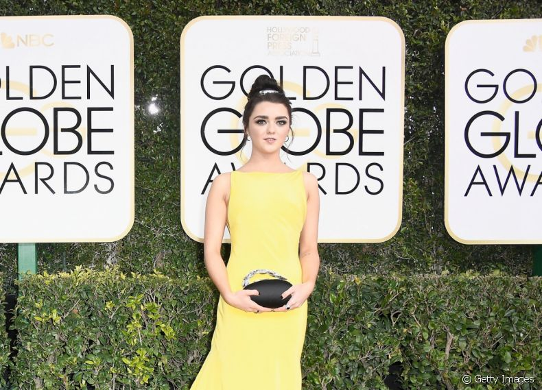 Maisie Williams, de 'Game Of Thrones', escolheu o vestido amarelo e o coque alto para o red carpet do Globo de Ouro 2017