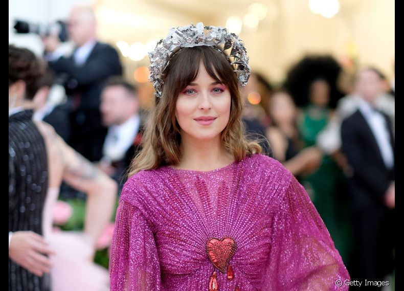 A franja cortina separada ao meio é uma marca do visual de Dakota Johnson